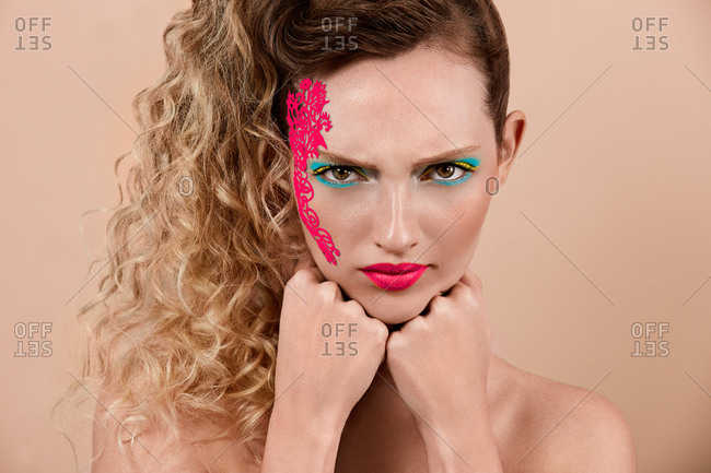 Dissatisfied young woman with colorful makeup and bright ornament on face keeping fists under chin and looking at camera against beige background