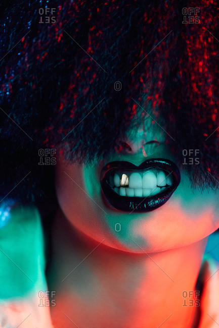 Crop female model in synthetic wig and with black lipstick showing teeth under colorful light