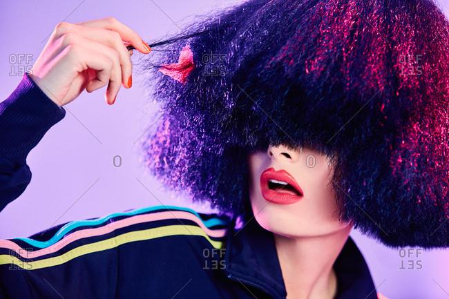 Astonished female in stylish sportswear inspecting fake hair under bright illumination against violet background
