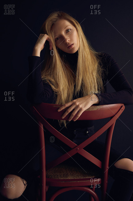 Young blond woman in dark clothes sitting on chair against black background and looking away