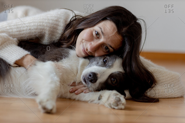Caring female in woolen sweater hugging funny Border Collie dog while lying on wooden floor together looking at camera