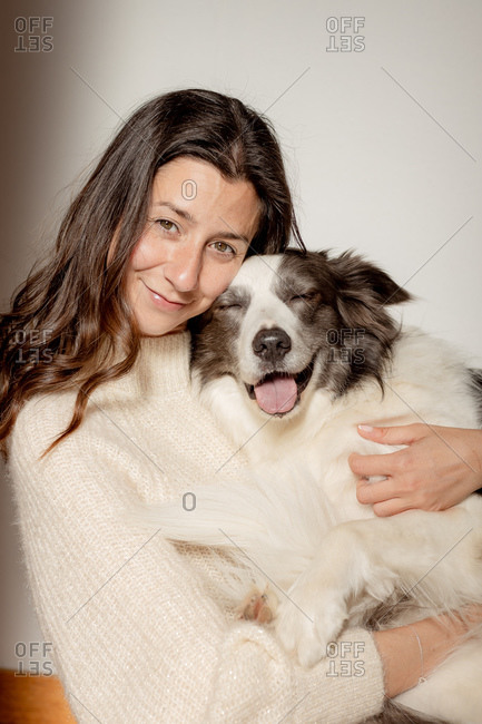 Caring female in woolen sweater hugging funny Border Collie dog while sitting on wooden floor together looking at camera