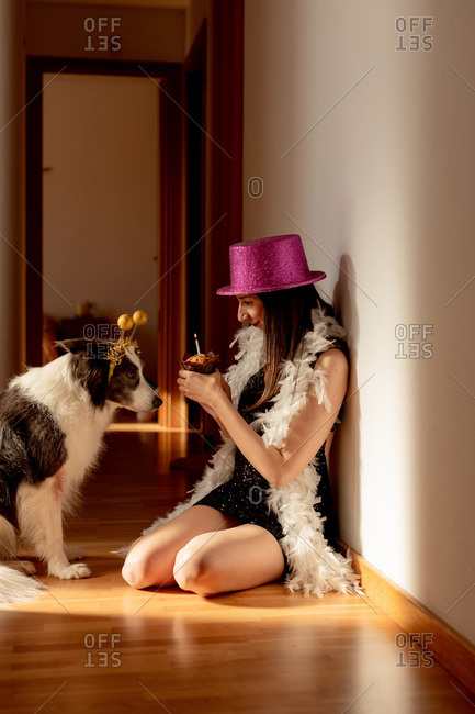 Side view of smiling female wearing party hat and dress sitting on floor with muffin and celebrating birthday together with dog during covid 19 pandemic