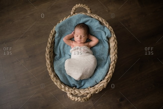 Top view of newborn baby wrapped in cloth lying on soft blanket and sleeping in wicker basket on floor at home