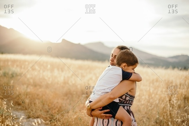 Adult woman hugging and carrying boy while resting in meadow against mountains and sundown sky in nature