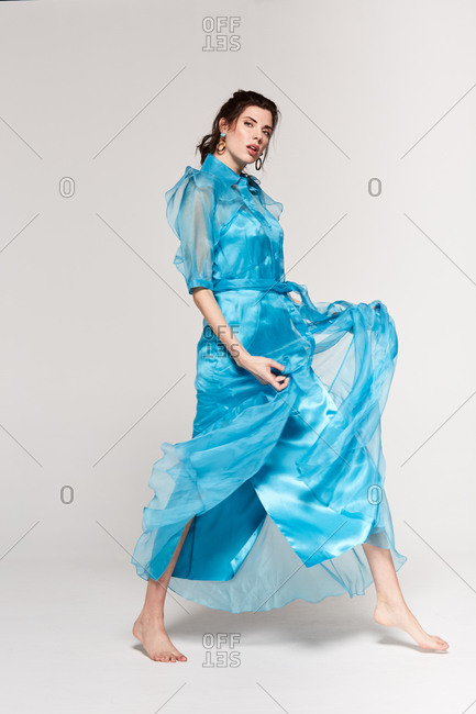 Full body of fashionable female with black hair in ponytail wearing light blue dress standing barefoot in white studio looking down