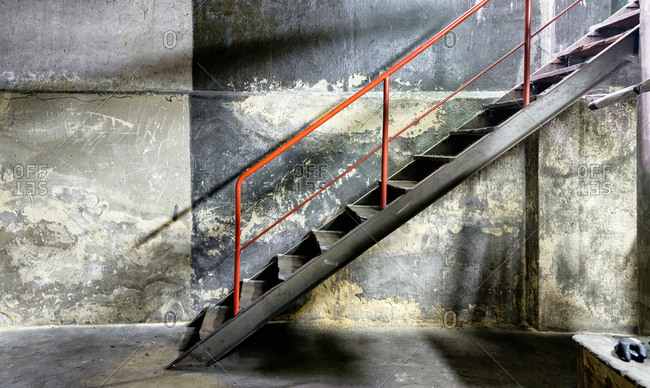 Side view of metal gray dusty staircase with red railing on background of old concrete shabby wall in abandoned factory