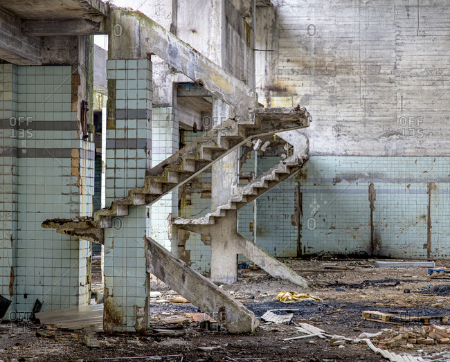 Concrete walls and remains of stairways in old abandoned industrial building with messy ground