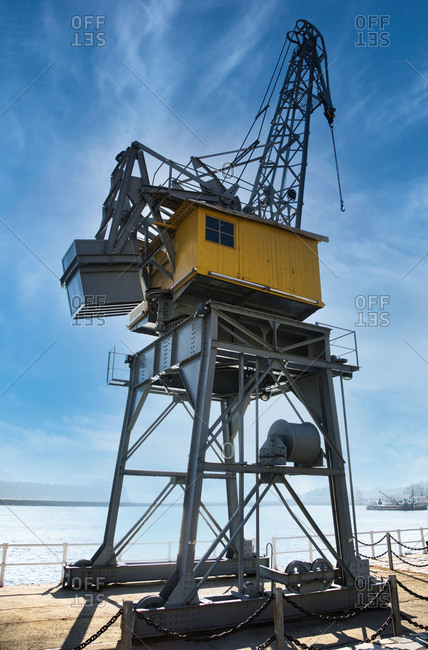 Low angle of contemporary container crane located on quay in Port of San Esteban de Pravia against cloudy blue sky on sunny day in Spain
