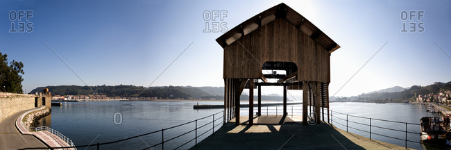 Wide angle view of wooden gazebo located on pier near tranquil sea water in Port of San Esteban de Pravia on sunny day in Spain