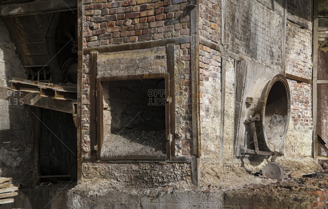 Dirty brick structure with trash located inside shabby workshop of derelict industrial facility