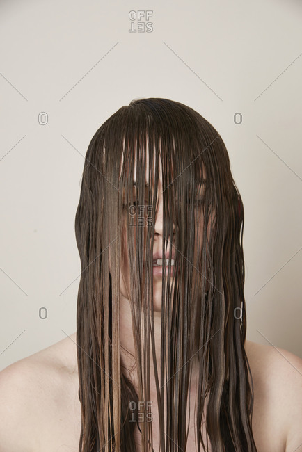 Young woman with long wet hair draped over her face