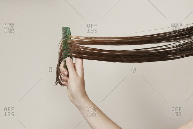 Young woman with long wet hair combing