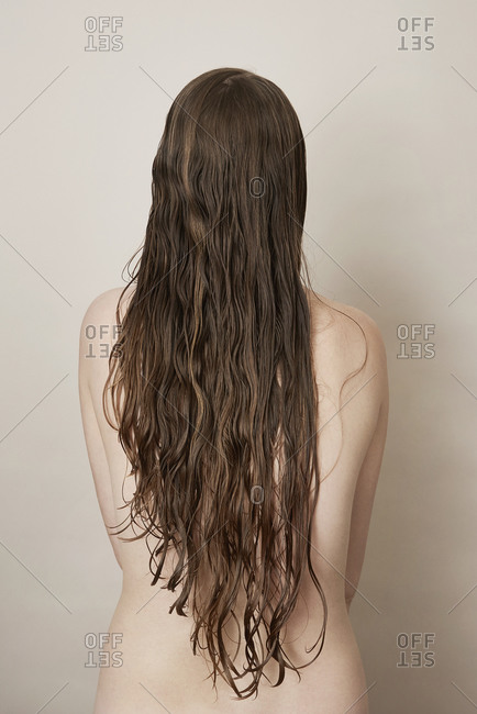 Rear view of young woman with long wet hair covering her nude backside
