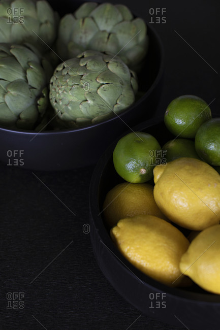 Bowl of citrus fruit beside a bowl of artichokes