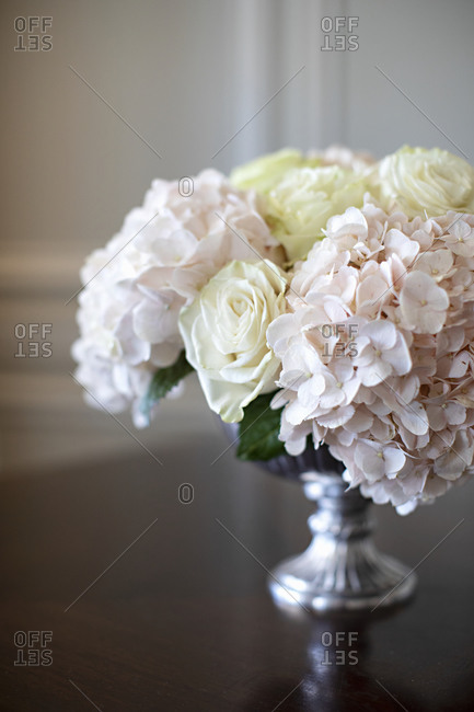 Silver vase filled with white roses and pink hydrangeas
