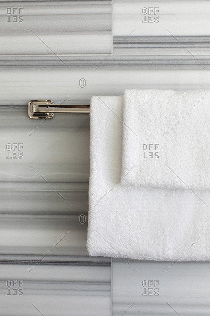 White towels folded neatly over a chrome towel bar in a bathroom