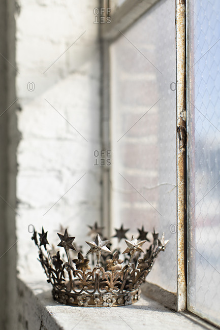 Tarnished crown on sill of old window
