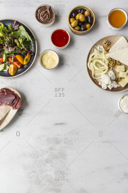 Healthy fresh breakfast ingredients on white marble surface