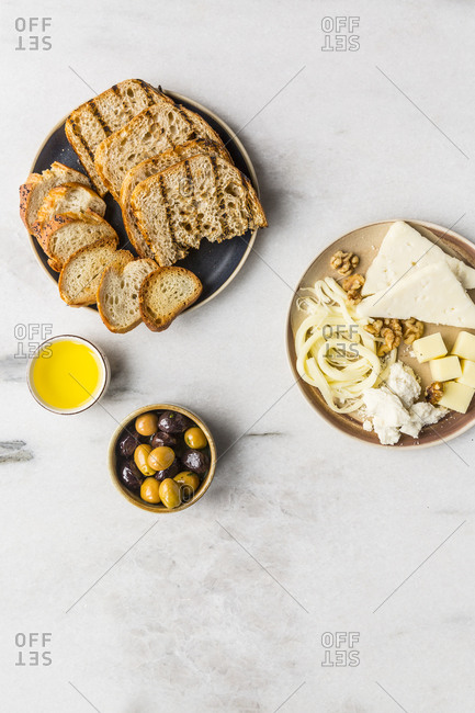 Cheese plate with olives, bread and olive oil