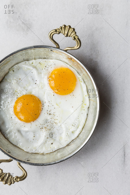 Overhead view of fried eggs in an antique skillet