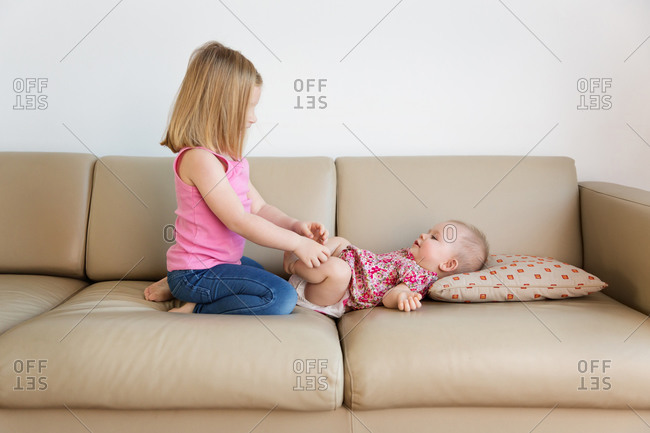 Young girl playing with baby sister lying on sofa at home
