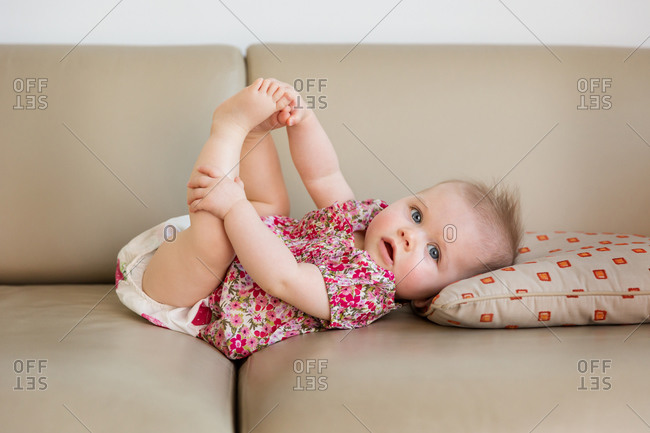 Cute baby girl lying on couch holding her feet