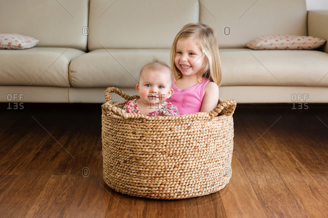 Playful toddler girl sitting with baby sister in basket at home
