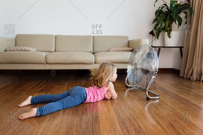 Little girl lying by electric fan on hardwood floor at home