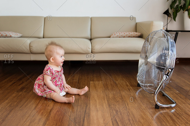 Funny baby sitting by electric fan on hardwood floor at home