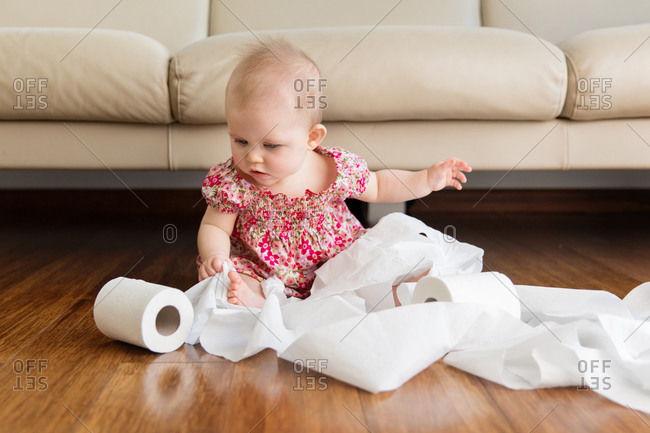 Baby girl playing with toilet paper on living room floor