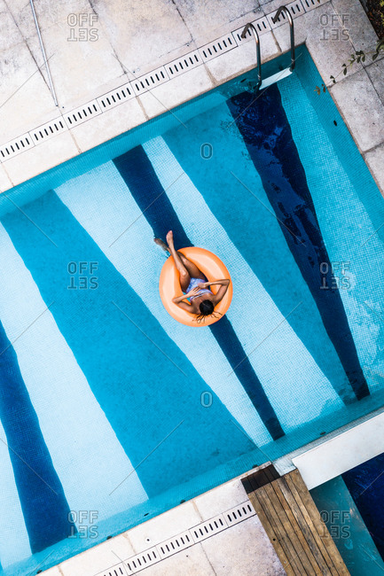 Aerial View Of Tanned Woman Floating Comfortably On Orange Inflatable Blow Up Ring In Luxury Villa Swimming Pool