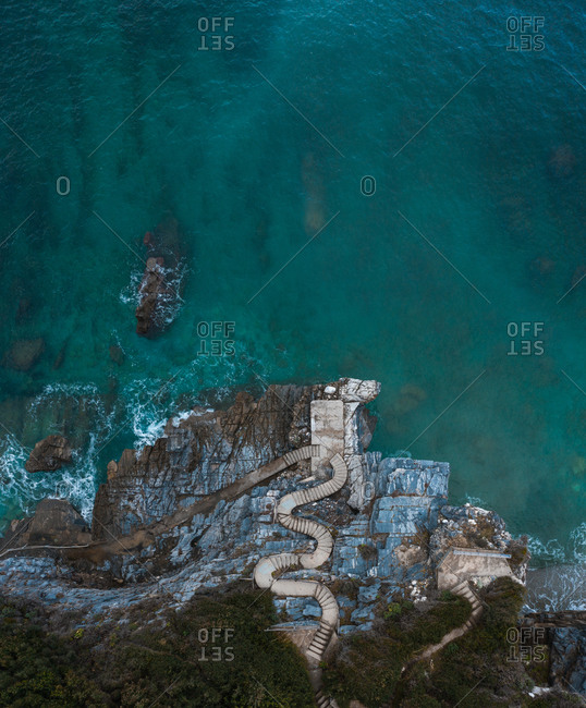 Aerial view of stairs on the shoreline in Milopotamos, Greece
