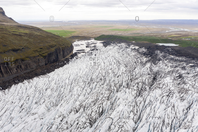 Aerial view of crevasses in the glacier surrounded by mountains in Svinafellsjokull, Iceland