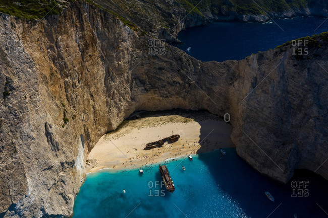 Aerial view of an abandoned boat on the shore of Navagio beach surrounded by turquoise water, Greece