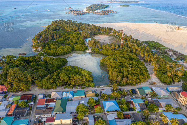 Aerial view of local island Huraa, North Male Atoll, Maldives, Indian Ocean with reclaimed land, mangroves and overwatervillas in the distance