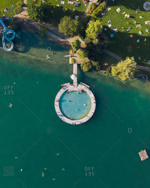Aerial view of an outdoor public pool that looks like the search logo. a slide in the shape of the g of google and some swimmer in Zurich Switzerland