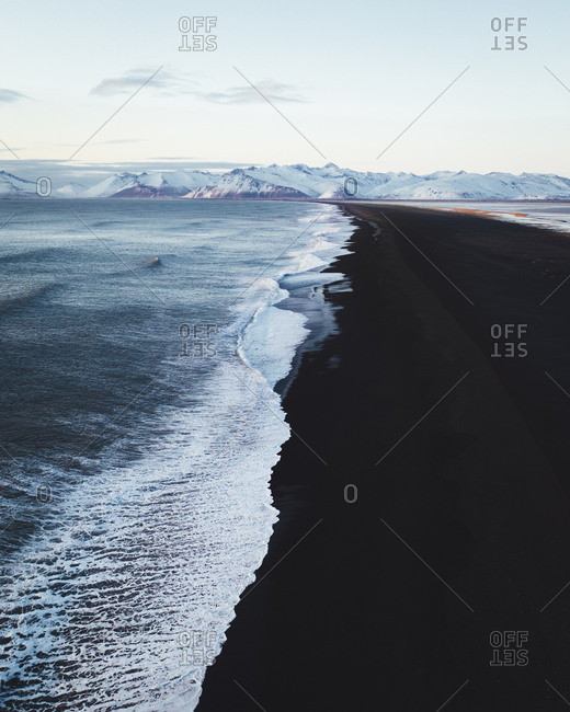 Aerial view of shoreline with snow capped mountains at Dyrholaey Viewpoint in Iceland