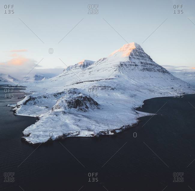Aerial view of a snowy mountain on the shore of the coast in Eastern Region, Iceland