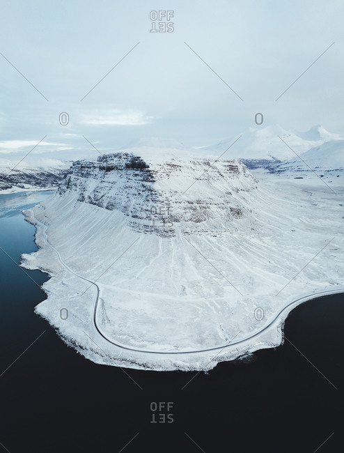 Aerial view of a snowy mountain on the shoreline in Reynivellir, Iceland