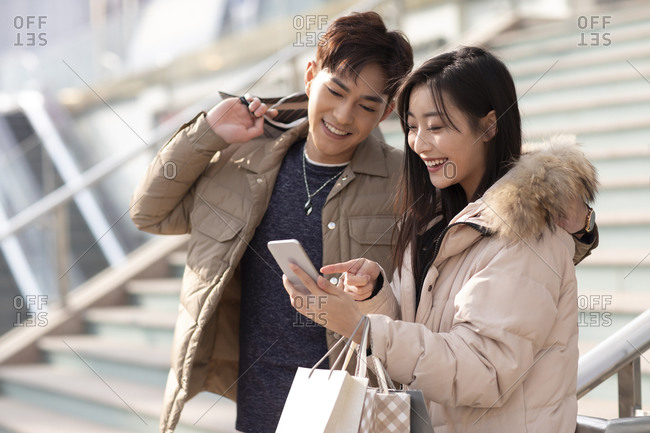 Happy young Chinese couple using smartphone outdoors