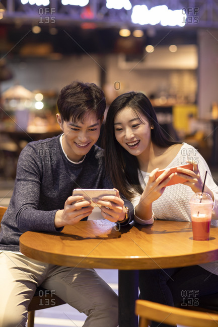 Happy young Chinese couple playing mobile games
