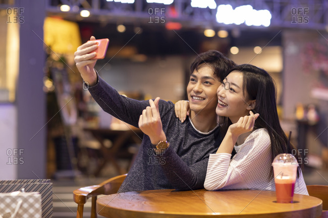 Happy young Chinese couple taking selfie with smartphone in shopping mall
