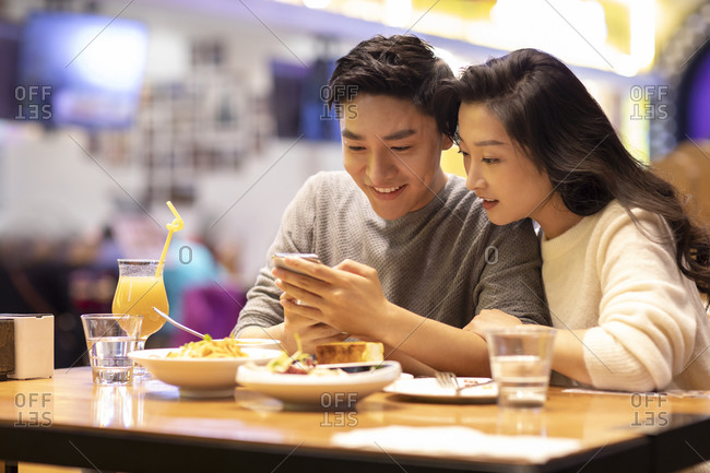 Happy young Chinese couple dating in restaurant
