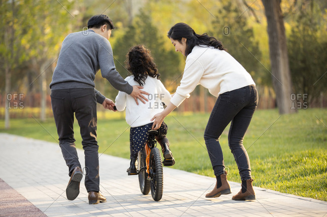 Chinese parents teaching child how to ride bike
