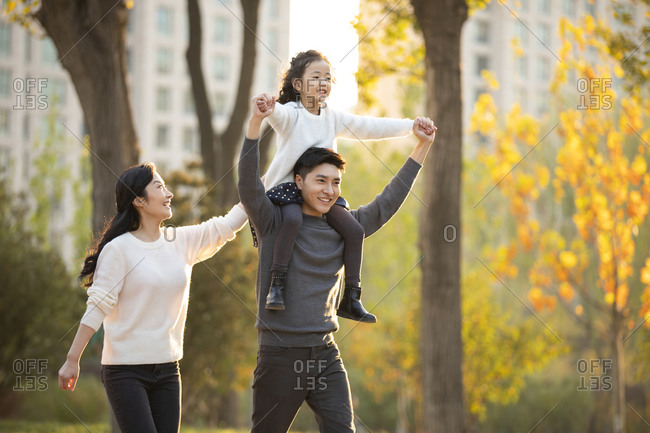 Happy young Chinese family having fun in park