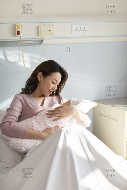 Young Chinese mother holding newborn baby in hospital ward