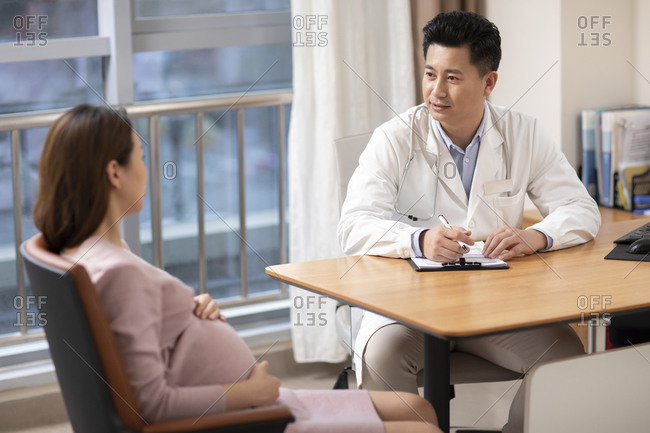 Chinese doctor talking with pregnant patient in office