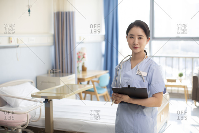 Young Chinese nurse in hospital ward