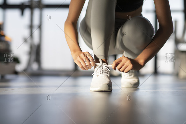 Young Chinese woman tying her shoelaces at gym